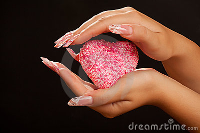 Human hands with manicure hold pink heart