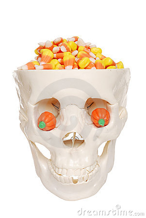 Human skull filled with candy corn and pumpkin eye