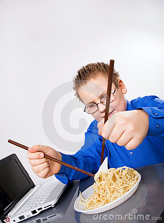 Hungry boy eating chinese noodles with sticks