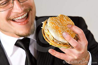 Hungry businessman eating hamburger