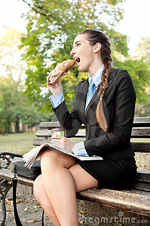 Hungry businesswoman in park