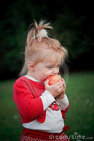 Hungry girl eating apple