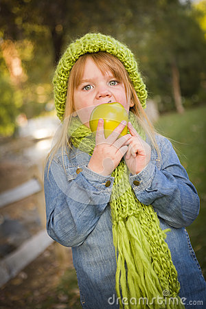 Hungry Girl Wearing Green Scarf and Hat Eating Apple Outside