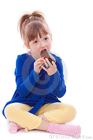 Hungry little girl eating cake