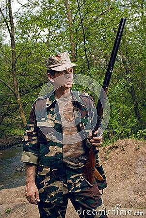 Hunter with gun in hands