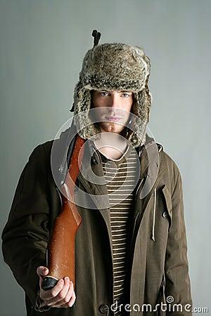 Hunter man fur winter hat holding rifle gun
