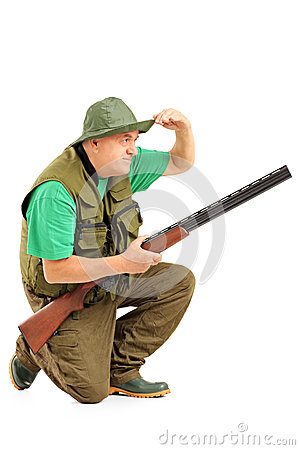 Hunter with rifle crouching and looking in the distance