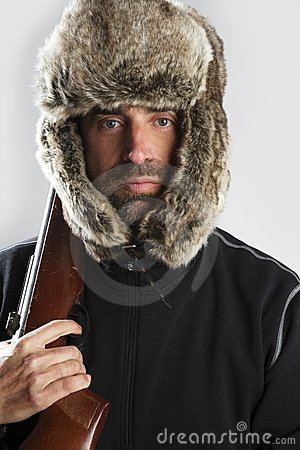 Hunter winter fur hat man holding gun
