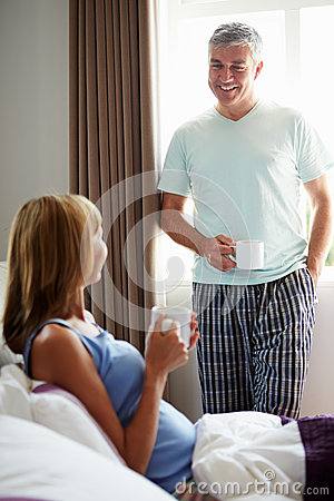 Husband Chatting With Wife Over Drink In Bed