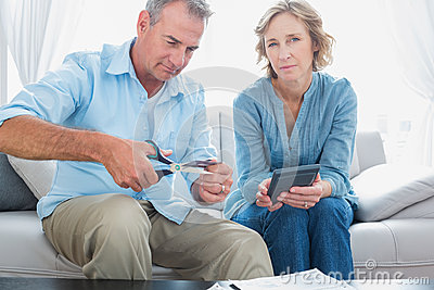 Husband cutting credit card in half with wife looking at camera