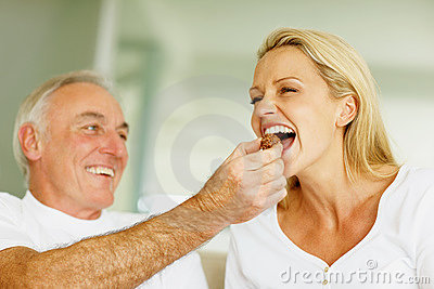 Husband feeding his wife with a piece of chocolate