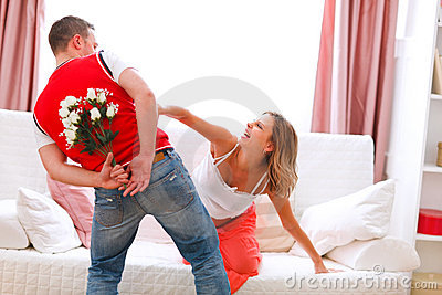 Husband hiding flowers from pregnant wife