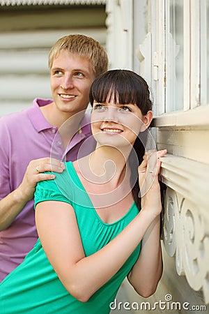 Husband hug wife near wooden village house