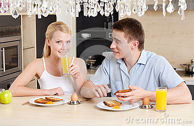 Husband and wife eat in the kitchen