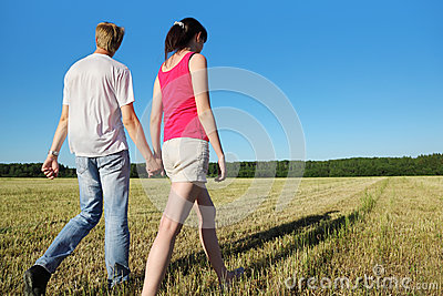 Husband, wife hold walk in field near wood