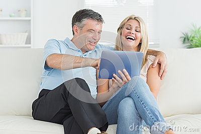Husband and wife laughing at tablet pc