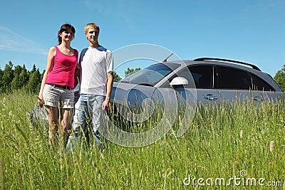 Husband, wife stand near car