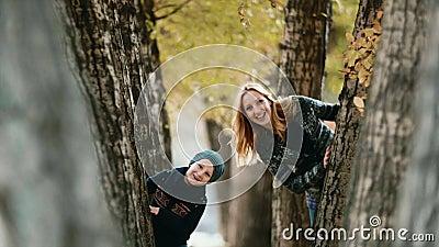 Hy-espião Movimento lento A cena está no parque entre as árvores do que o movimento da mãe e do filho atrás das árvores video estoque