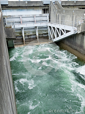 Hydro dam control weir with underneath discharge