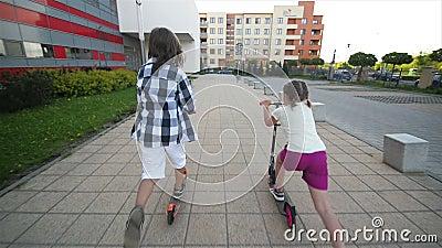 I bambini imparano guidare il motorino il giorno di estate soleggiato Gioco dei bambini all'aperto con i motorini Svago attivo e  stock footage