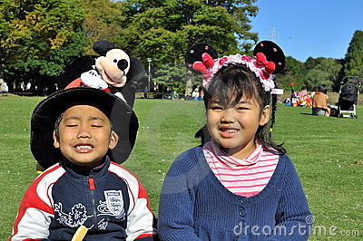 I fratelli germani con il grandi cappello di Mickey e capelli di Minnie legano Immagine Stock Editoriale