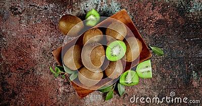 I kiwi freschi con foglie su piastra di legno ruotano lentamente stock footage
