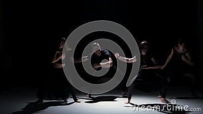 I movimenti contemporanei sensuali di ballo di cinque ballerini sul nero, ombra stock footage