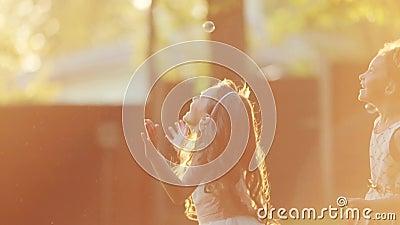 I piccoli bambini europei sono saltanti e giocanti con le bolle di sapone ad una luce del tramonto Chiarore della lente, fucilazi video d archivio
