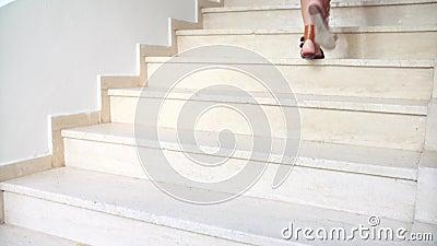 I piedi femminili abbronzati giovani in sandali salgono le scale stock footage