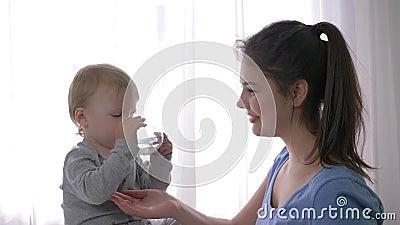 I primi successi del bambino, ragazzo felice del bambino beve indipendente l'acqua minerale da vetro accanto alla giovane madre s archivi video