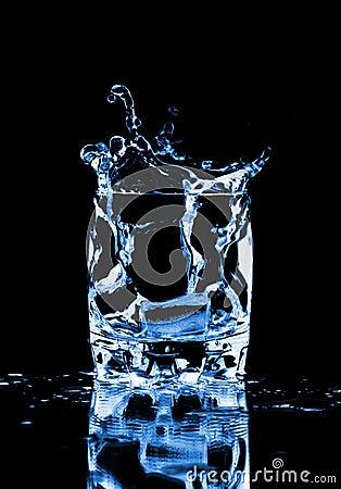 Ice cube splashing into glass of water