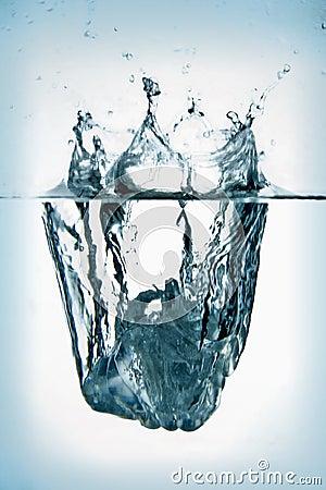 Ice cube splashing into water.