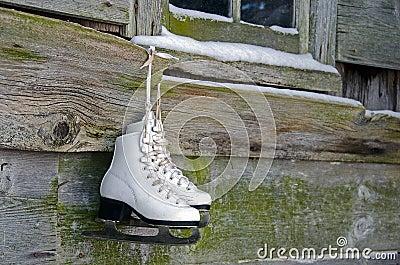 Ice skates hanging on barn