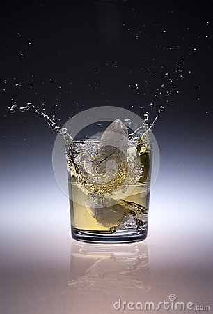 Ice splashes in beverage.