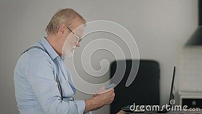 Idade moderna, idoso ocupado em óculos pagando contas online usa laptop e um telefone celular enquanto se senta em uma mesa video estoque