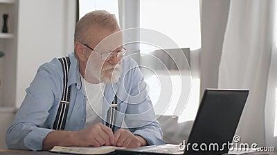 Idade moderna, pensionista atraente com barba cinzenta em óculos paga contas de utilidade trabalhando online no computador video estoque