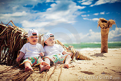 Identical twin boys relaxing on a beach