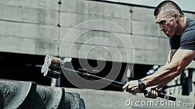 Idrottens muskelträningsman träffar däcket med en hammare i närheten, kastar hammare, motivation och sport lager videofilmer