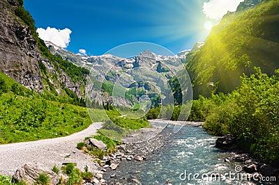 Idyllic alpine valley in sun rays.
