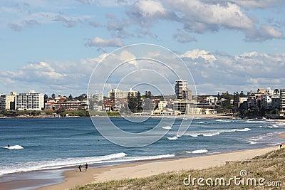 Idyllic beach bay with town