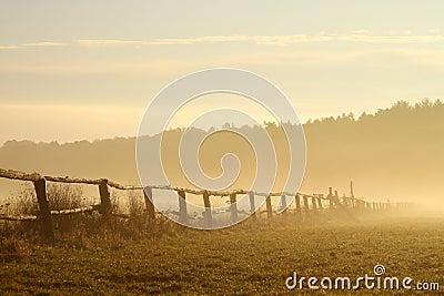 Idyllic fence on a misty field at sunrise