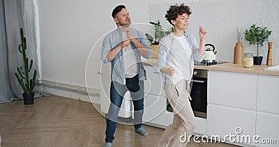 Iemand zingt in een lepel dansen in de keuken met een vrouw die plezier heeft in muziek stock footage