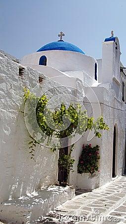 Iglesia griega con el árbol verde