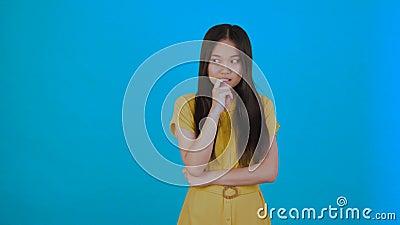 Ik heb een idee. Aziatisch meisje kwam met een geweldig idee en is blij en danst geïsoleerd op blauwe achtergrond 4.000 stock footage