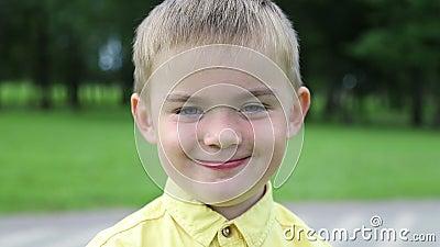 Il bambino è un ragazzo triste, poi diventa allegro e ride, primo piano stock footage