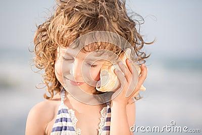 Il bambino felice ascolta la conchiglia alla spiaggia