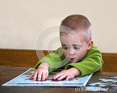 Bambino che lavora ad un puzzle.