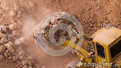 Il caricamento dell'escavatore di vista superiore ha schiacciato la roccia sull'autocarro con cassone ribaltabile archivi video