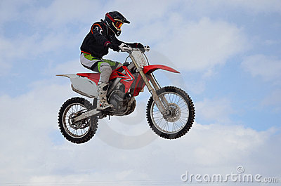 Il cavaliere di motocross salta, cielo blu