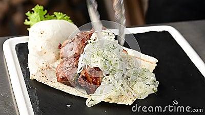 Il cuoco pone la carne arrostita su un piatto archivi video